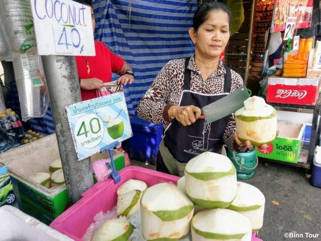 vendor at Chatuchak opening a coconut