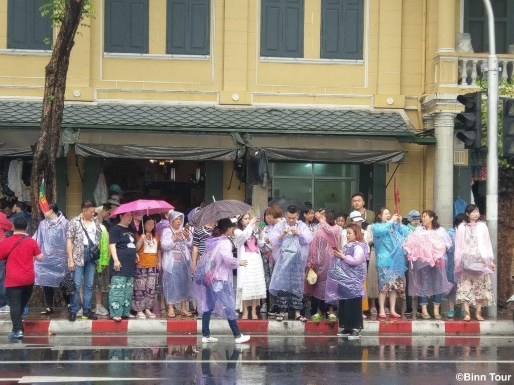 Besucher in Bangkok mit Schirmen und Regenjacken