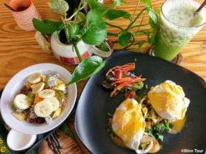 breakfast at the Unnamed including eggs benedict, juice and fruits