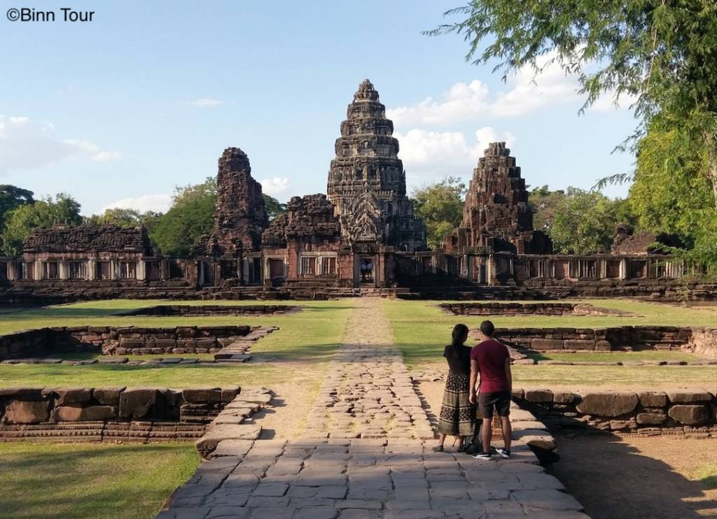 two people looking at an ancient Khmer temple in Phimai